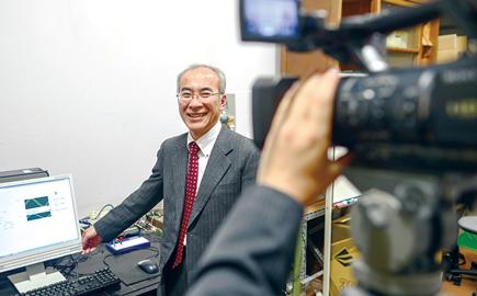 小林教授がパソコンと並んで撮影カメラに微笑んでいる写真。